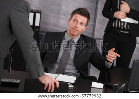 Mid adult manager sitting at desk in office training employee.? - stock photo
