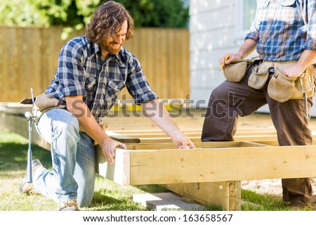 Mid adult manual workers working on wooden frame at construction site - stock photo