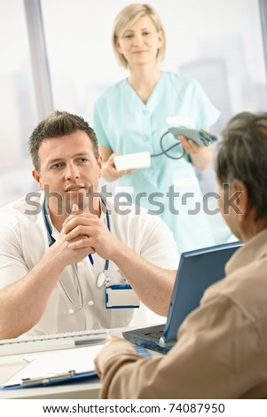 Mid-adult medical doctor talking to elderly patient, nurse holding blood pressure gauge in background. - stock photo