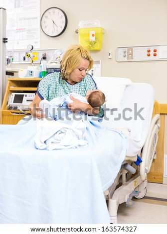 Mid adult mother looking at newborn baby while sitting in bed at hospital - stock photo