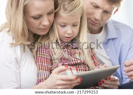 Mid adult parents using tablet PC with daughter at home - stock photo