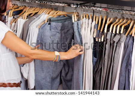 Mid adult woman choosing trouser from rack in clothing store - stock photo