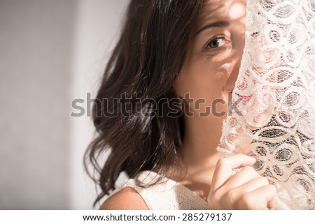 Mid-adult woman hiding her face behind curtain - stock photo