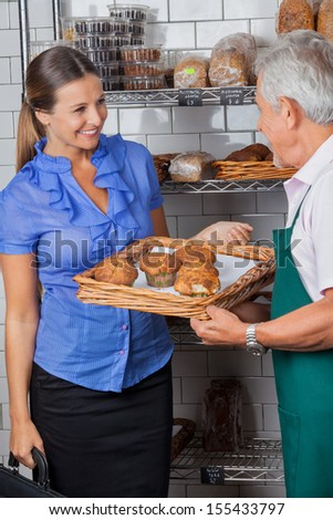 Mid adult woman looking at senior salesman holding tray of muffins at grocery store - stock photo