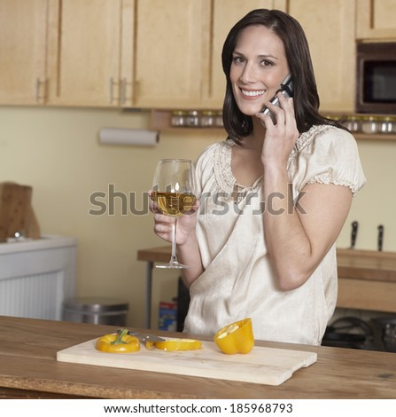Mid-Adult Woman on Phone While Cooking - stock photo