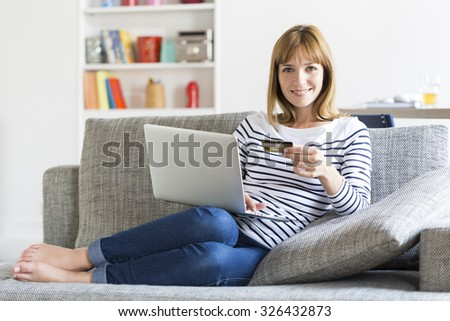 Mid adult woman shopping using laptop and credit card in modern apartment. Ecommerce - stock photo