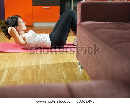 mid adult woman training abdominals at home. Horizontal shape, full length, side view, copy space - stock photo