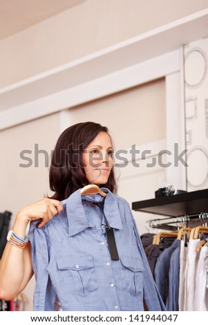Mid adult woman trying shirt while looking away in clothing store - stock photo