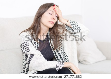 Mid-adult woman with headache on coach - stock photo