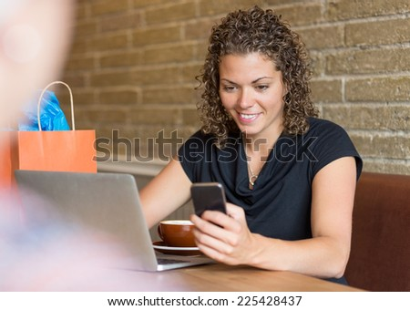 Mid adult woman with laptop on table text messaging through mobilephone in cafeteria - stock photo