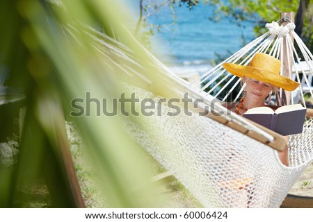 mid adult woman with orange hat reading book on hammock. Front view, Horizontal shape, copy space - stock photo