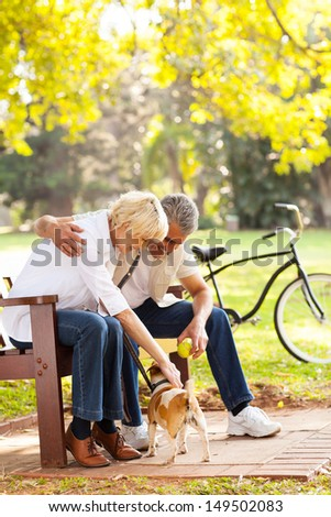 mid age couple playing with pet dog outdoors - stock photo