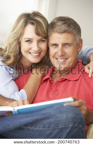 Mid age couple reading book together - stock photo