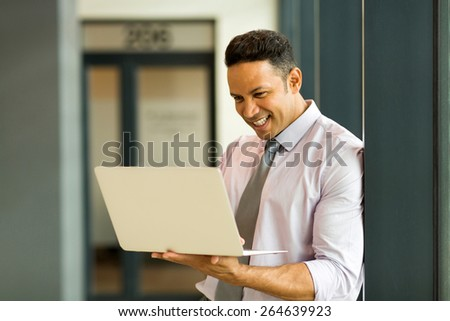 mid age office worker working on laptop in modern office - stock photo