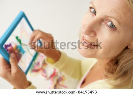 Mid age woman doing cross stitch - stock photo