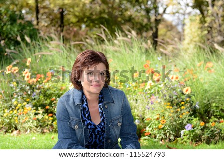 Mid age woman looking at camera in garden - stock photo