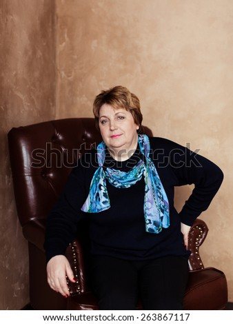 Mid age woman sitting in a chair at home - stock photo