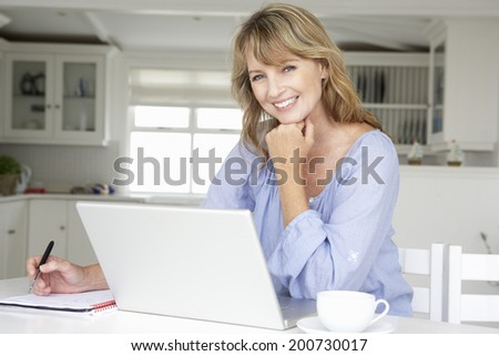 Mid age woman working at home on laptop - stock photo