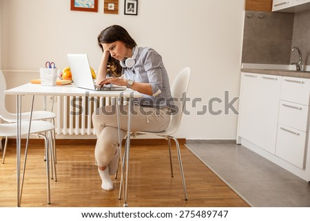 Mid age woman working on her blog.She sitting in he lliving room - stock photo