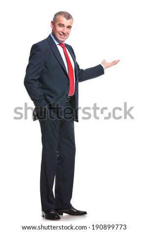 mid aged business man presenting something in the back while holding a hand in his pocket and smiling for the camera. isolated on a white background - stock photo
