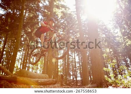 Mid-Air Shot Of Man Riding Mountain Bike Through Woods - stock photo