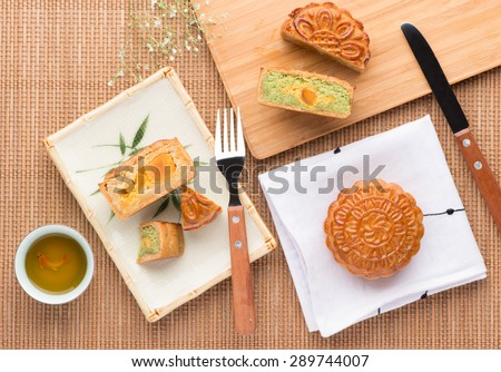 Mid-Autumn Festival moon cake on wooden board. Mooncake and tea,Chinese mid autumn festival food. angle view from above - stock photo