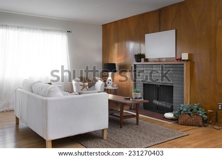 Mid Century Living Room, craftsman style with framed fire place, wooden table, rug and white couch. - stock photo
