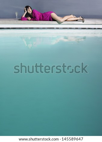 Mid distance shot of a young woman reclining by the pool with champagne glass - stock photo