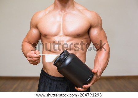 Mid section of a body builder holding a scoop of protein mix in gym - stock photo