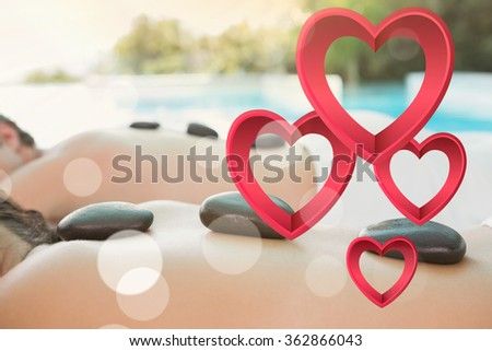 Mid section of a couple enjoying stone massage against pink hearts - stock photo