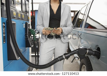 Mid section of a female counting money while waiting for refueling the tank of car - stock photo