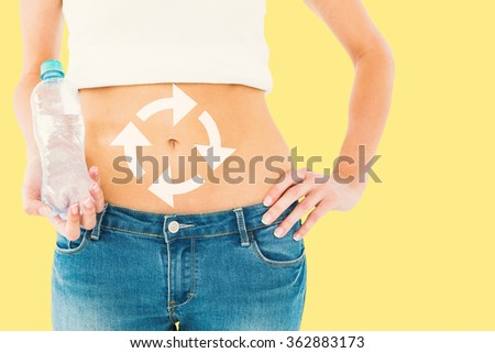 Mid section of a fit woman holding a bottle of water against yellow background - stock photo