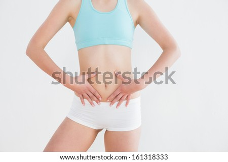 Mid section of a fit woman in sportswear with hands on belly against wall in fitness studio - stock photo