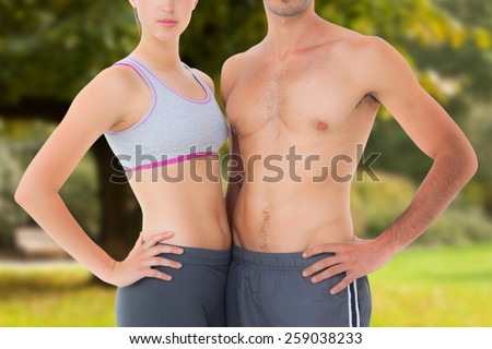 Mid section of a fit young couple against trees and meadow in the park - stock photo
