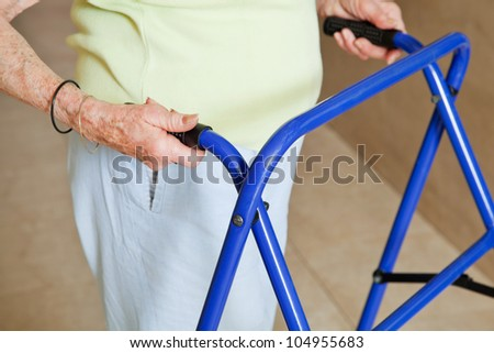 Mid section of a senior woman using blue walker - stock photo