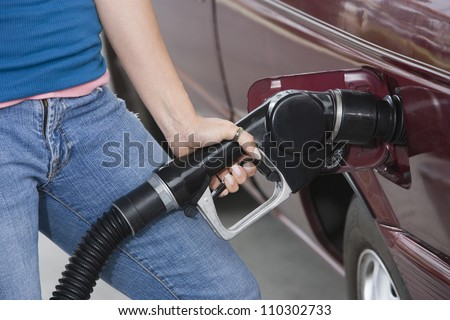 Mid section of a woman refueling her car at a fuel station - stock photo