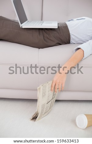 Mid section of a young woman with laptop and news paper lying on sofa at home - stock photo