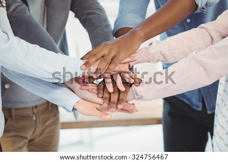 Mid section of business team putting their hands together at office - stock photo