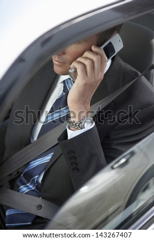 Mid section of businessman using mobile phone in car - stock photo
