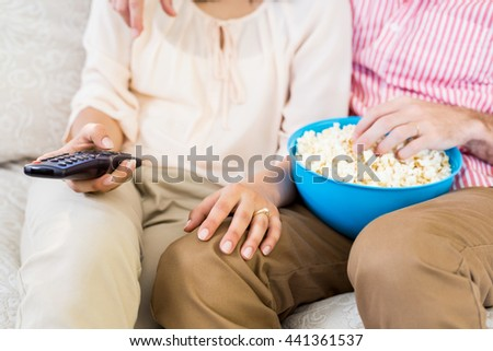 Mid section of couple sitting on sofa watching television and having popcorn - stock photo