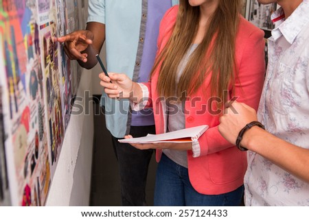 Mid section of creative business people pointing at photos in office - stock photo