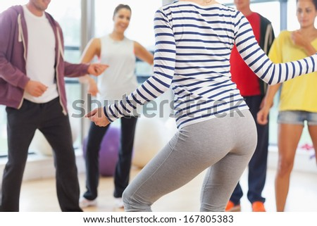 Mid section of fitness class and instructor doing pilates exercise in bright room - stock photo