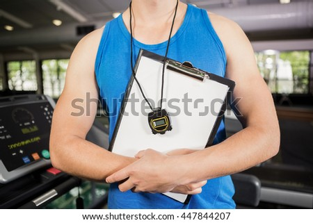 Mid section of trainer standing in gym with clipboard and stopwatch - stock photo