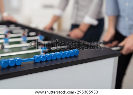 Mid section of two people wearing shirts with rolled up sleeves playing foosball, focus on foreground - stock photo