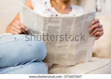 Mid section of woman reading newspaper on the sofa - stock photo