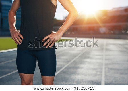 Mid section shot of male athlete standing on race track with his hands on hips on a bright sunlight. Cropped shot of young man runner on athletics running track in stadium. - stock photo