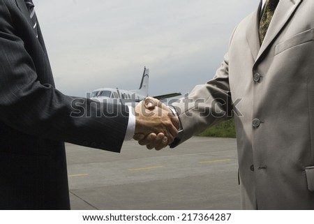 Mid section view of two businessmen shaking hands - stock photo