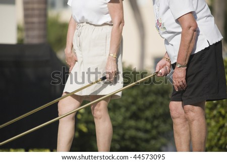 Mid section view of two senior women playing shuffleboard - stock photo