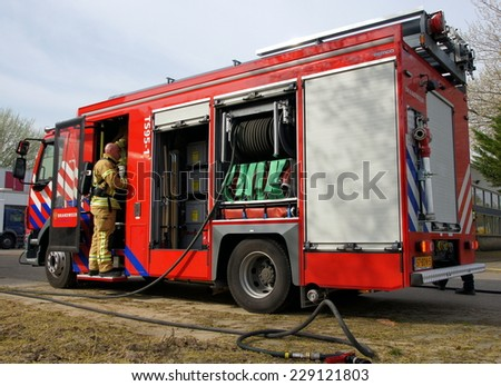 MIDDELHARNIS , THE NETHERLANDS - APRIL 1 , 2014 ; fire truck and firefighters during a exercise on the street in the Netherlands - stock photo