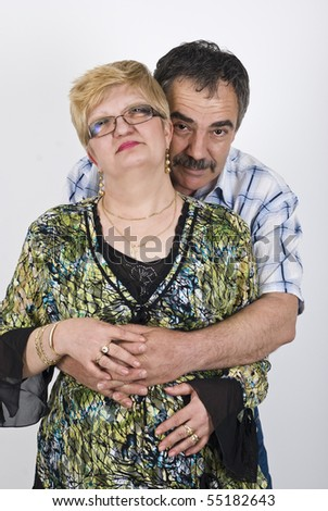 Middle adult couple standing in a hug and smiling - stock photo